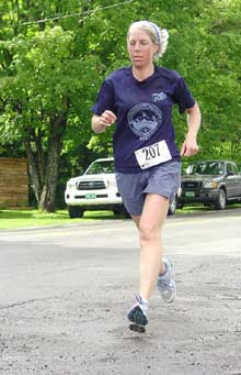 A road runner runs the Runaway Pond Road Race in Glover Vermont